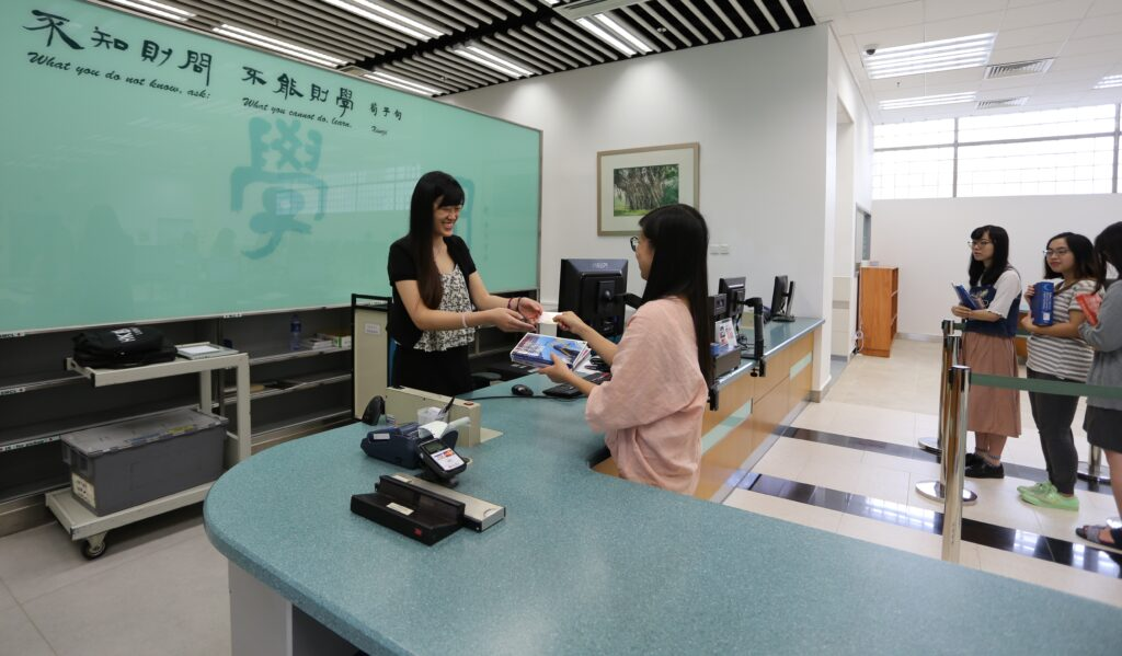 Picture of a student checking out books at the User Services Counter