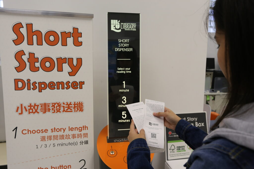 Student holding a short story printout with the short story dispenser in the background