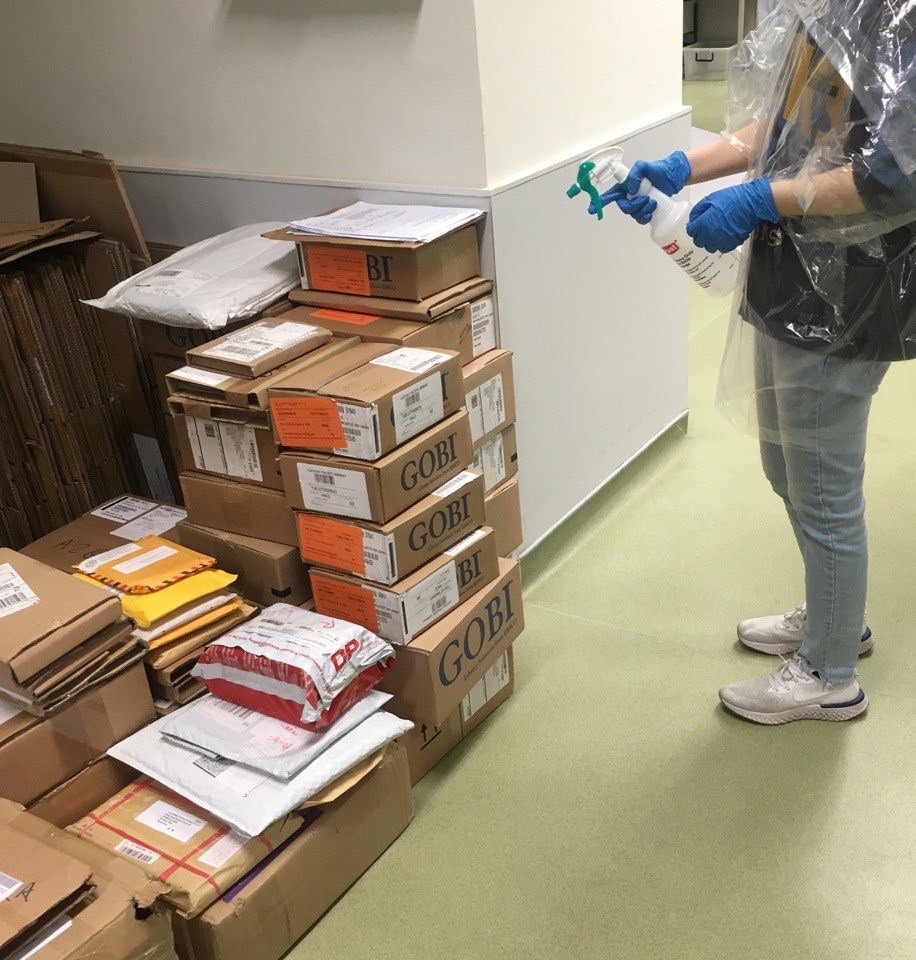 A library staff disinfects book packaging